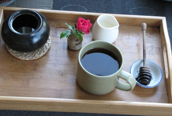 Bamboo tea tray with a bowl of agave, a wild rose in Sefla's homemade vase, a white mini-pitcher of milk, and a wooden honey stirrer in a Japanese fish bowl