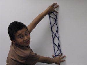 The string figure Jacob's Ladder by José T., shown against a white board with his proud smiling face looking back at us